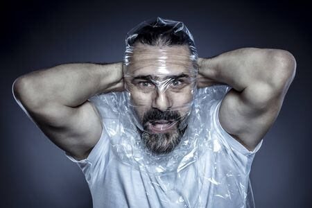 portrait of a man with a beard and his face wrapped in a plastic film. concept of toxicity of plastic materials and their excessive use in common life.