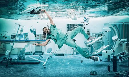 Smiling doctor floats under water in a flooded operating room.