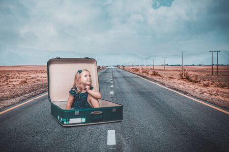 little girl sitting in an old suitcase on a road dreams of an adventure. Travel and freedom concept.