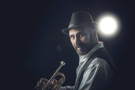 jazz trumpet player on a dark background. Portrait performed in the studio 스톡 콘텐츠