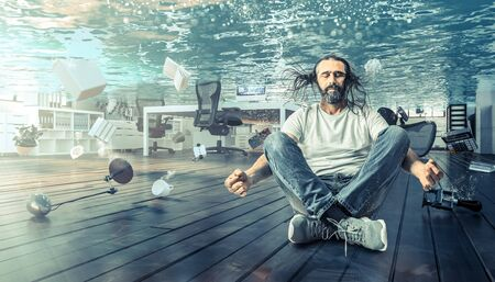 man sitting underwater who relaxes in a yoga position. Office completely flooded. Concept of problems and calm.