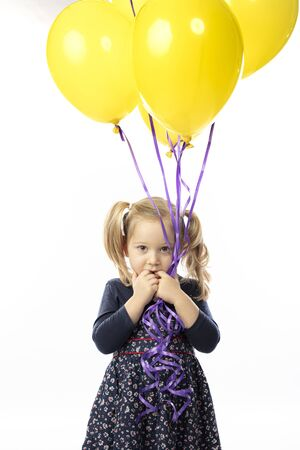 portrait of a little blond girl holding yellow balloons. Concept of carefree and childhood. 스톡 콘텐츠