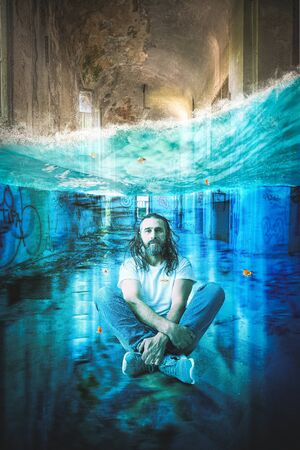 man with long hair and beard meditates underwater in a long abandoned building. Concept of calm in complicated situations. 스톡 콘텐츠