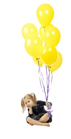 bored little girl sitting on the floor holding colorful balloons in hand. Isolated on white. 스톡 콘텐츠
