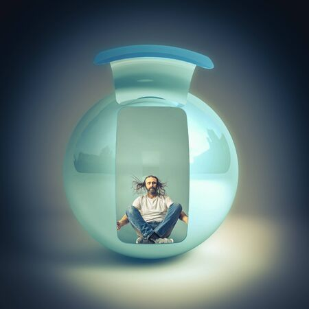 man with long hair sitting inside a sphere meditates with his eyes closed. comfort zone concept.
