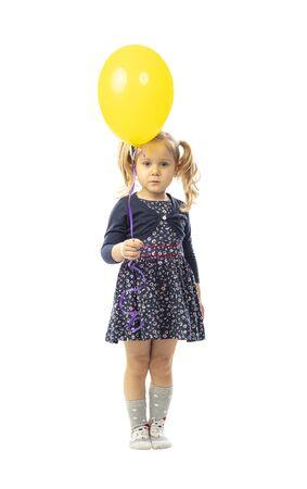 portrait of isolated blonde little girl holding yellow ballon