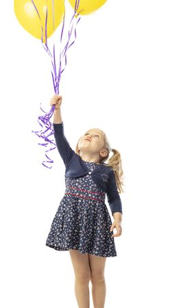 blonde little girl with yellow balloons looks up. isolated on white background