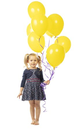 portrait of a smiling blonde 3 year old girl holding a group of yellow balloons. isolated on white 스톡 콘텐츠