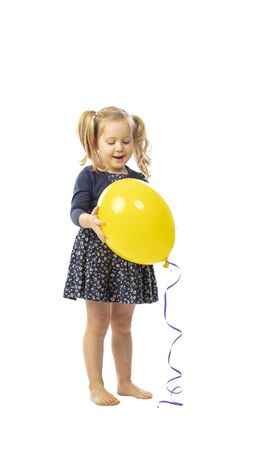 standing little girl holds a yellow balloon, happy and satisfied expression. isolated on white background. 스톡 콘텐츠