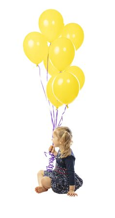 portrait of a sitting 3 year old girl holding a group of yellow balloons. side view. isolated on white
