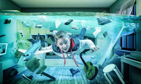 6 year old caucasian child plays happy with an airplane in his flooded room. Surreal image, concept of light-heartedness.