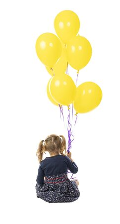 portrait of a sitting 3 year old girl holding a group of yellow balloons. seen from behind. isolated on white 스톡 콘텐츠