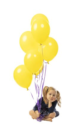 portrait of a 3 year old caucasian girl sitting and with colorful balloons. bored expression. isolated on white. 스톡 콘텐츠