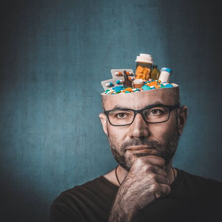 Portrait of man with glasses and hand on chin. Thoughtful look. Abstract image, head full of medicines. Concept linked to the ethical and excessive use of medicines.