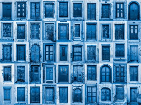 composition of various ancient residential doors in the city of oia in santorini, greece. diversity concept. blue shades and no one around.