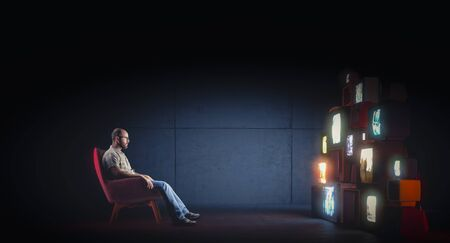 Caucasian man with glasses sitting on an armchair watching several vintage televisions broadcasting different programs. Concept of alienation, dependence on the mass media. Solitude.