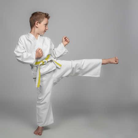 child intent on performing a martial arts kick. studio photos.