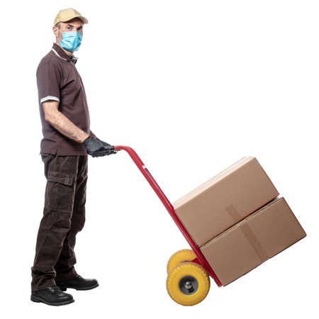 Man courier with mask uses a handtruck to transport packages. isolated on white. concept of health and safety in shipments.
