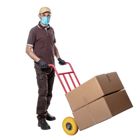 delivery man with mask for covid-19. handtruck with packages. isolated on white. work safely.
