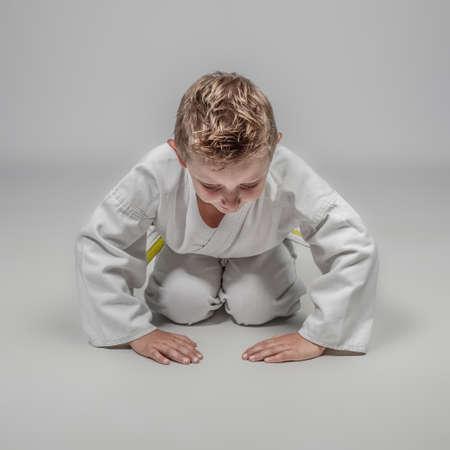 child practicing martial arts in rei position. studio shot