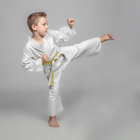child practicing karate in kick position. studio shot. 版權商用圖片