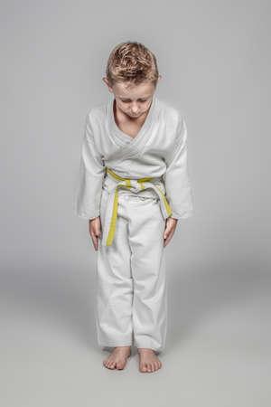 seven year old caucasian child practicing martial arts. Rei position. studio shot.