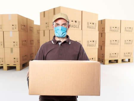 courier with mask and parcel in hand, pallet of cartons in the background.