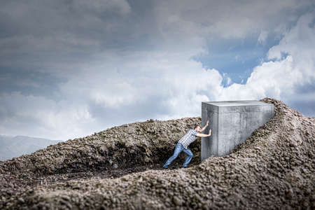 man pushes a huge concrete cube crawling into the ground. concept of determination and strength. 版權商用圖片