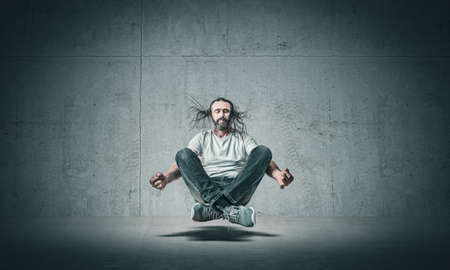 man with long hair meditating suspended in the air.
