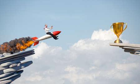 businessman uses a rocket to reach an award. concept of determination. 版權商用圖片