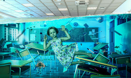 little girl floating under water in a flooded classroom. concept of difficulty in education.