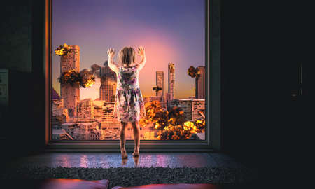 little girl looks out of the window at a burning city. destroyed buildings, explosions. apocalypse concept. 版權商用圖片