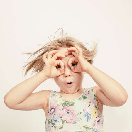 little girl with hands over her eyes to simulate glasses