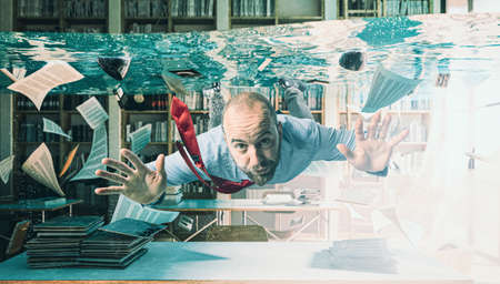 businessman swimming in a flooded office