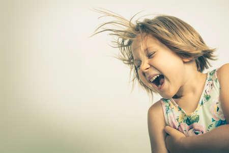 cheerful little girl laughs carefree. studio portrait