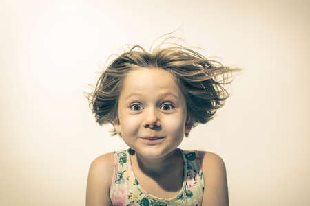 little girl looks in camera with funny and amused expression. studio portrait 版權商用圖片