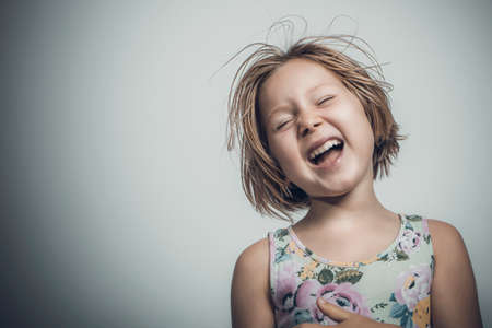caucasian little girl with short hair laughing carefree. studio portrait