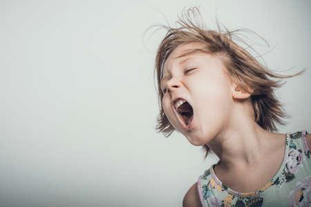 blond caucasian little girl screams.studio shot