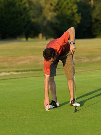 A golfer picking up his ball. photo