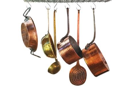 utencilios de cocina: cacerolas que cuelgan de un estante en una cocina de estilo tradicional
