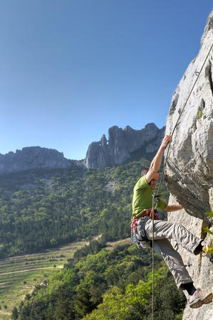 young man rock climbing in french photo