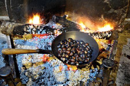 castaÑas: castañas asadas en la chimenea, la tradición francesa Foto de archivo