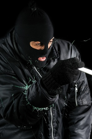 a burglar who broken the glass of a window to enter photo