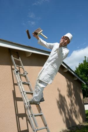accident de travail: un peintre en b�timent qui travaille tombe de l'�chelle