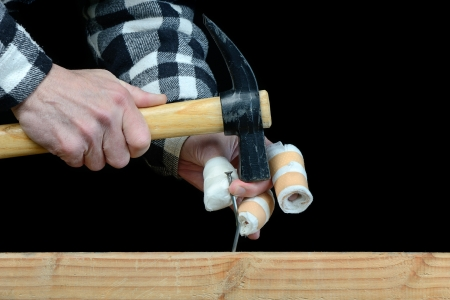 clumsiness: a handyman awkward trying to hammer a nail Stock Photo