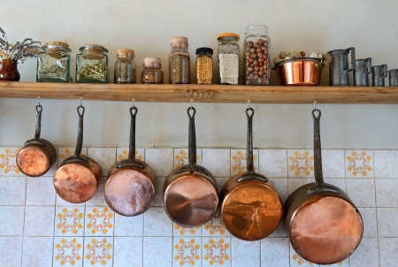 Old saucepans hanging from in a traditional-style kitchen photo