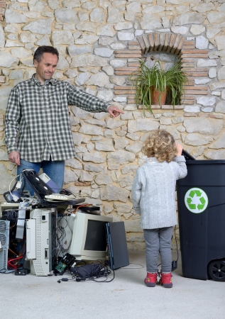 pile reuse: a father who shows her child a good example for recycling old computer equipment Stock Photo
