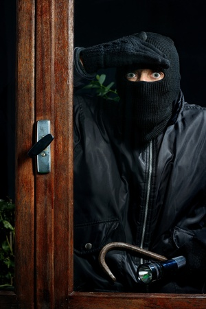 malefactor: a burglar trying to enter through a window Stock Photo