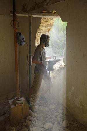 demolishing: a builder that creates a door in an old stone wall Stock Photo