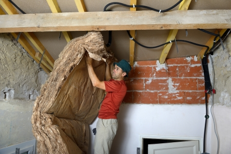 rock wool: a worker who insert the ceiling insulation
